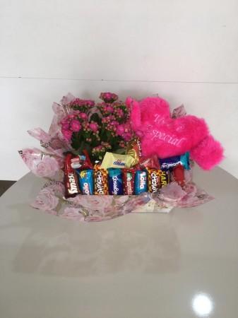Cesta de flor com chocolate e coração de pelúcia